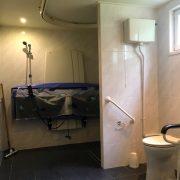 Rolstoeltoegankelijk Chalet Zuid Limburg, badkamer met douchestoeltje en douchebrancard aan de wand