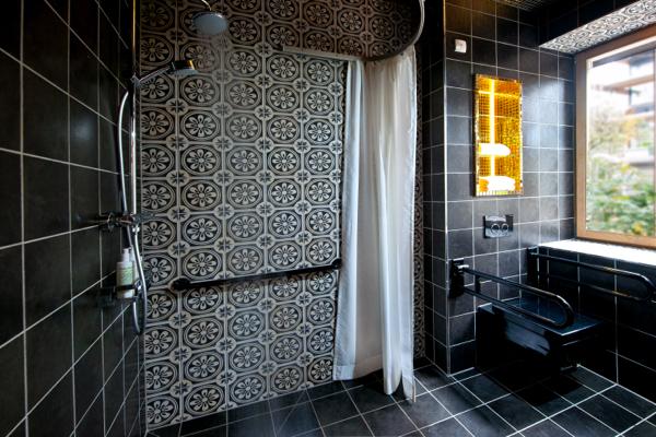 Ruime en mooie badkamer, beugels bij de toilet.