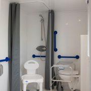 Doucheruimte met douchestoel, beugels in douche en bij toilet