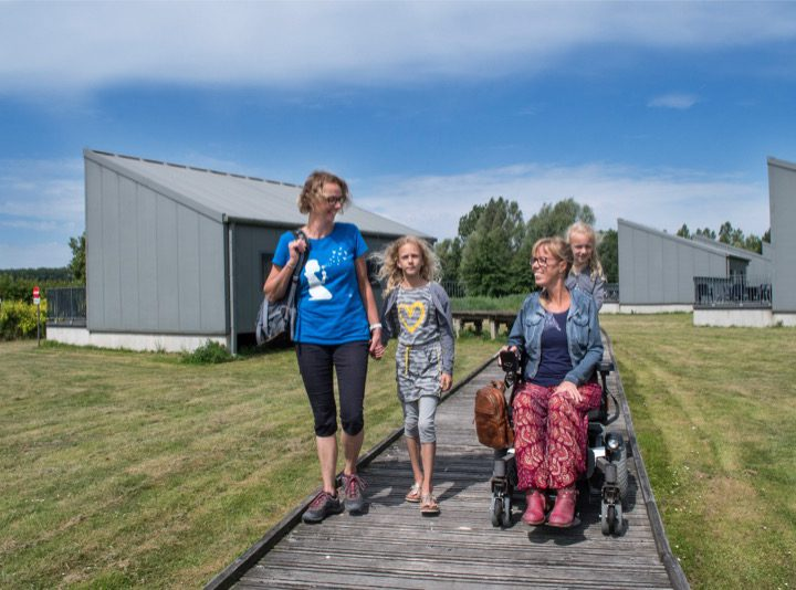Eelke met vriendin en kinderen voor de rolstoeltoegankelijke bungalow op Provinciaal domein de Gavers