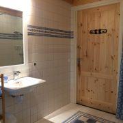witte tegels, blank houten deur, sfeervol verlicht