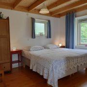 Tweepersoonsbed met sprei, nachtkastjes en twee ramen met blauwe gordijnen. Houten kledingkast