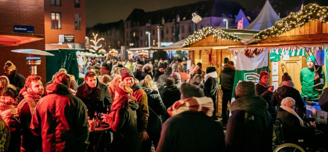 Mensen in het donker op de kerstmarkt
