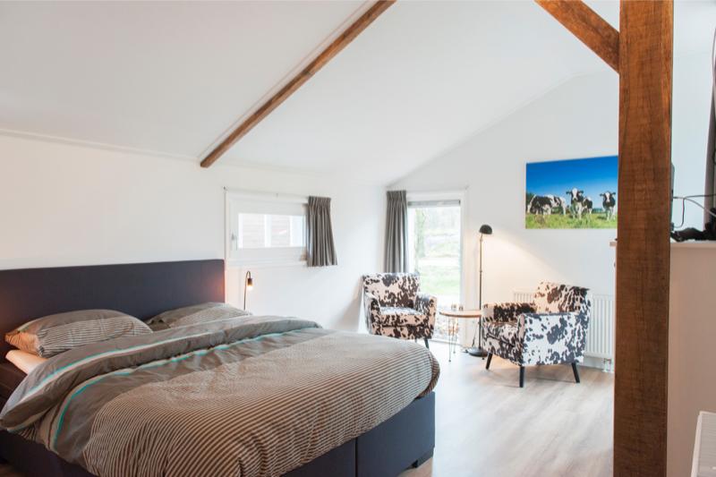 bed met twee stoeltjes (koeienprint) voor het raam