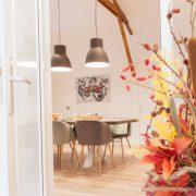 bloemen op de voorgrond, achtergrond houten eettafel met stoelen