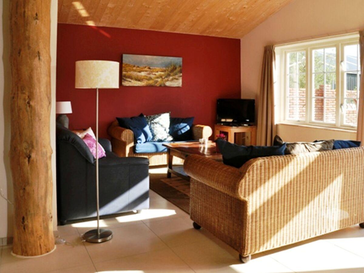 woonkamer met 3 banken, warm rode muur, dikke houten steunpaal,