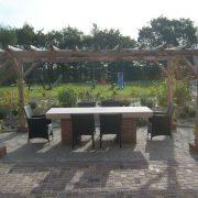 Grote tafel met stoelen onder pergola