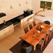 grote witte keuken met zwart aanrechtblad, klein stuk onderrijdbaar, grote houten tafel met stoelen