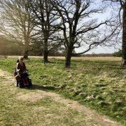 Eelke in haar elektrische rolstoel op een wat hobbelige graspad (holtingerveld) lang een rij bomen met weids uitzicht