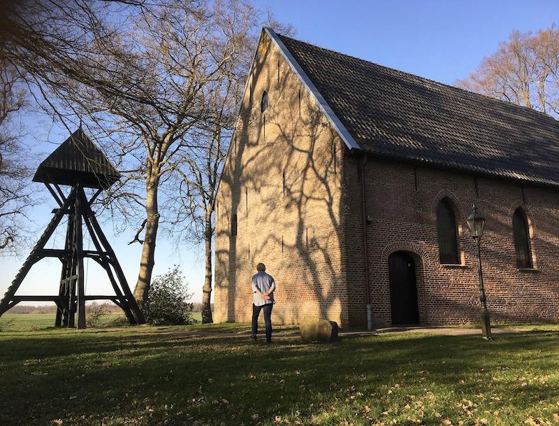 Kerkje met houten Klokkentoren in het veld met wat bomen er om heen