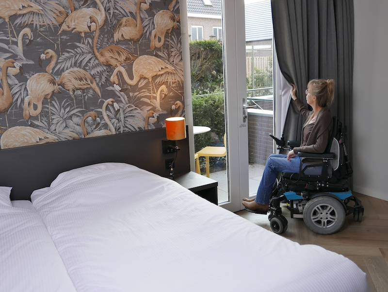 Eelke staat in haar rolstoel bij de openslaande deuren en doet het gordijn open, naast het bed. Ze kijkt naar buiten naar een klein terras met tafeltje en gele stoeltjes