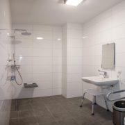 witte tegels aan de wand, grijze tegels op de grond, regendouche met zitje, onderijdbare wastafel en toilet met beugels