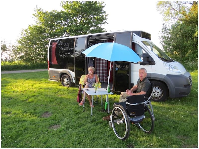 man in rolstoel met vrouw op campingstoel zitten voor een camper met groot glazen wand op een grasveld onder een blauwe parasol