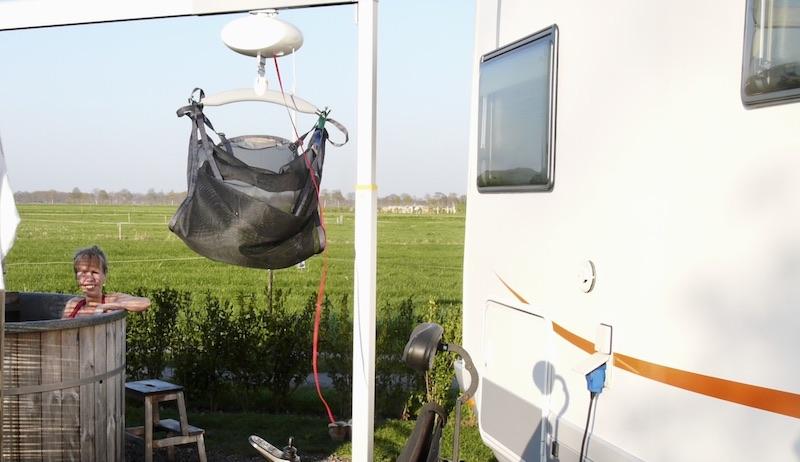 In zit naast een camper in een hottub met op de voorgrond een tilliftsysteem aan een staande beugel over de hottub heen
