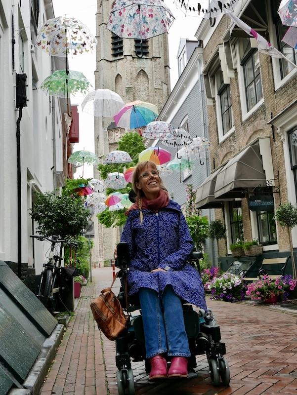 Eelke in haar rolstoel in een knus ogende steeg met op de achtergrond ene kerktoren en in de lucht paraplu's hangend aan touwen tussen de gebouwen