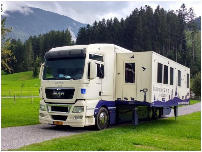 Grote vrachtwagencamper met uitschuifbaar zijkant in de bergen op groen grasveld