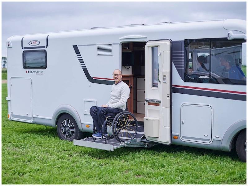Man in handbewogen rolstoel kom aan de zijkant van een camper met een liftje naar beneden