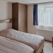 twee bedden naast elkaar met een raam en blauwe gordijnen