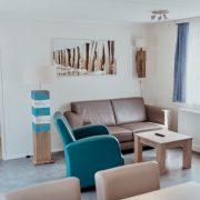 woonkamer met beige bank, twee blauwe stoelen en een houten salontafel. Boven de bank een schilderij van een strand
