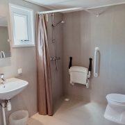 badkamer met Linidodouchestoel aan de wand, toilet met beugels in de hoek, onderrijdbare wastafel
