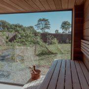Saunabankjes op de voorgrond met zicht naar buiten door grote ramen