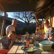 De Vos, buiten eten aan de picknicktafel, familie van Eelke met twee kindjes en drie volwassenen in de zon lachend