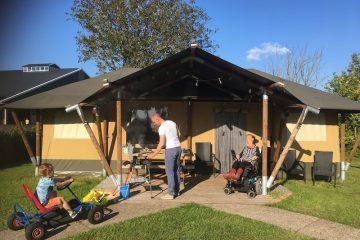 Eelke ligt in haar rolstoel voor de tent in de zon, haar neefje komt aanrijden op de skelter en zwager maakt de BBQ aan