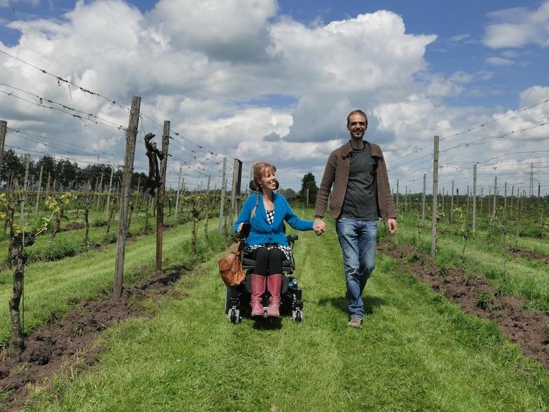 Eelke in rolstoel en Tjeerd hand in hand met aan beide kanten druiventakken