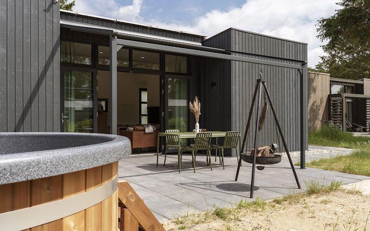 Zwart houten huisje, voorkant met terras en driepoot met vuurschaal (andere hoek)